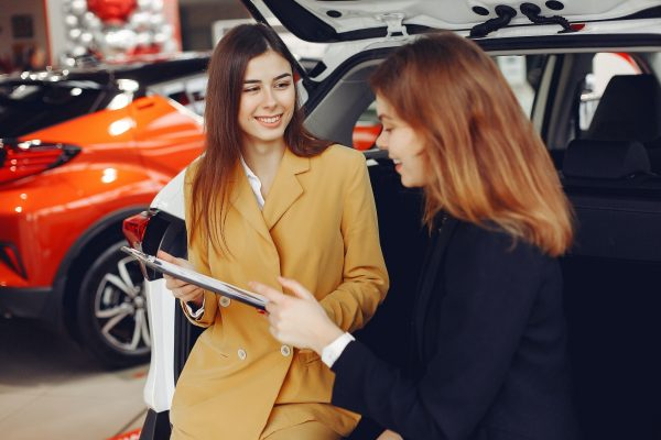 Two women negotiating a car sale